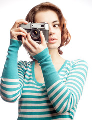 Attractive brunette aims her camera, isolated on white