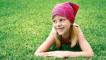 little girl lying on green grass in the summer park