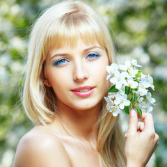 Happy young blue-eyed blonde woman posing with flowers in hand