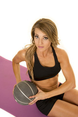 fit woman in black shorts and top with ball twisting top view