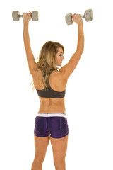 fit woman in purple shorts back with weights up