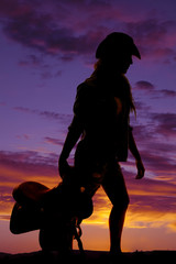 silhouette of a cowgirl holding a saddle behind her