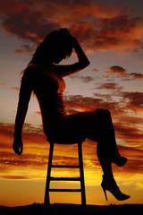 silhouette of a woman sitting in a white dress head down