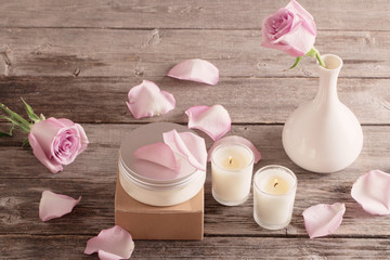 cosmetic cream with pink roses and candle  on old wooden table