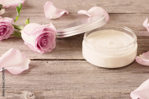 Sliko cosmetic cream with pink roses on old wooden table