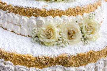 Torta di nozze con panna e granella di nocciole decorata da rose