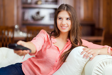 Happy young woman watching tv on sofa