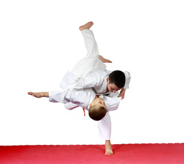 On a red mat athletes are training judo throws