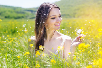 Beautiful girl with dandelion in yellow field