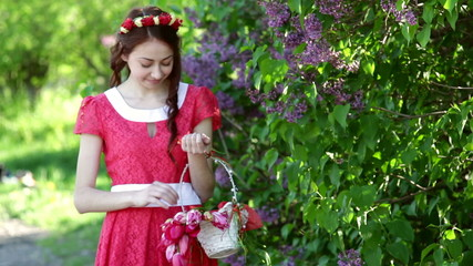 beautiful woman in a red dress walks in the park
