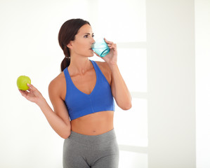 Slim energetic woman drinking a glass of water