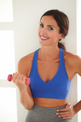 Slim lady doing exercise with dumbbell