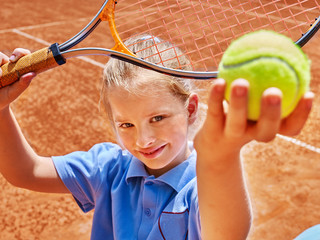 Child with racket and ball on  tennis court