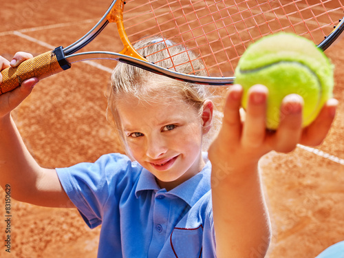 Fototapeta Child with racket and ball on tennis court