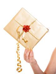 Female hand holding golden gift box isolated
