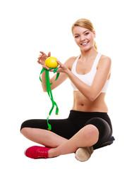 Joyful woman holds grapefruit and measurement tape