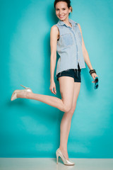 Summer fashion girl in jeans shirt shorts and high heels.