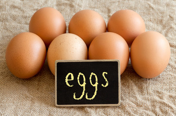 Chicken eggs and small chalkboard