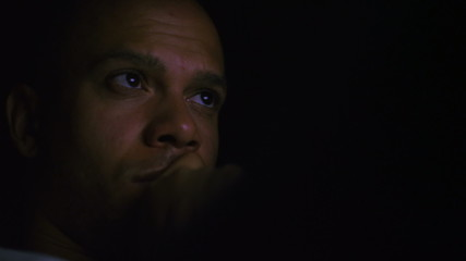 Man on his laptop at night reviewing something