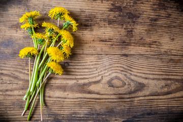 Dandelions on brown wood texture