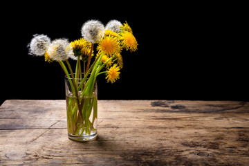Dandelions in glass on wood table