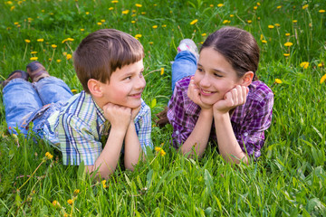 Two kids on green grass meadow