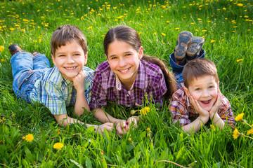 Three kids on green grass meadow