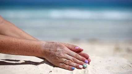 Woman is pouring sand through her fingers