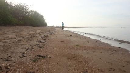brunette girl runs on beach turns round at dawn
