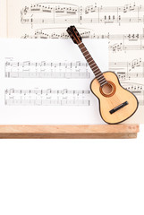 SMALL ACOUSTIC GUITAR WITH MUSIC SCORE