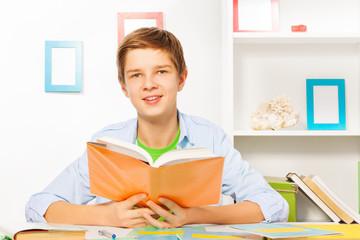 Nice handsome boy read orange book and do homework