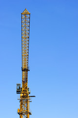 Construction yellow crane tower isolated on blue sky