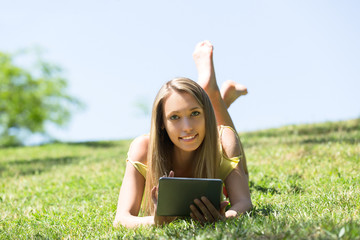 Girl relaxing outdoor with tablet