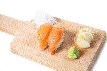 Japanese salmon sushi on a wooden cutting board with ginger and