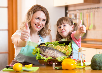 kid and mother show thumb up cooking in kitchen