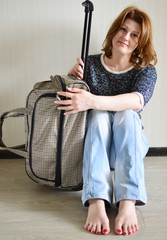 Positive woman with travel bag sitting by  wall