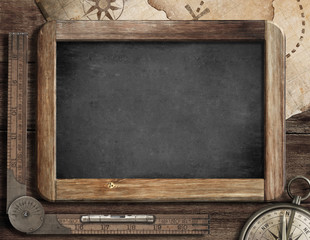 Vintage blackboard with treasure map, old compass and ruler
