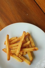 French fries in white plate on brown background.