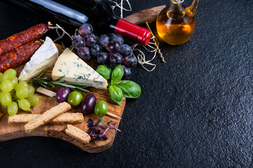Tapas board with cheese,olives,grapes and red wine