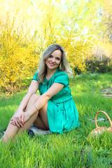 Beautiful girl sitting on the green lawn.