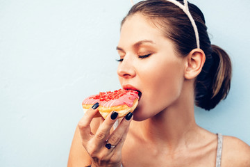 Attractive brunette sexy woman eating tasty donut