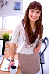 Young attractive fashion designer standing by desk in office