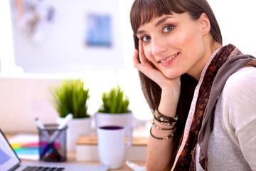 Portrait of attractive female fashion designer sitting at office