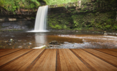 Beautiful woodland stream and waterfall in Summer with wooden pl