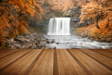 Beautiful woodland stream and waterfall in Autumn Fall with wood