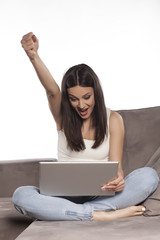very happy young woman on the sofa with a laptop on her legs