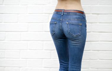 Beautiful woman body in denim jeans on white brick wall backgrou
