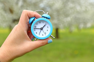 Hand holding an alarm clock with abstract nature background