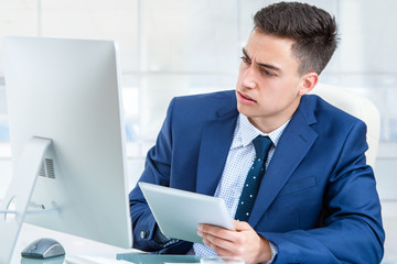 Businessman synchronizing digital tablet with computer.