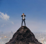 young business man standing on top of mountain and spying by bin